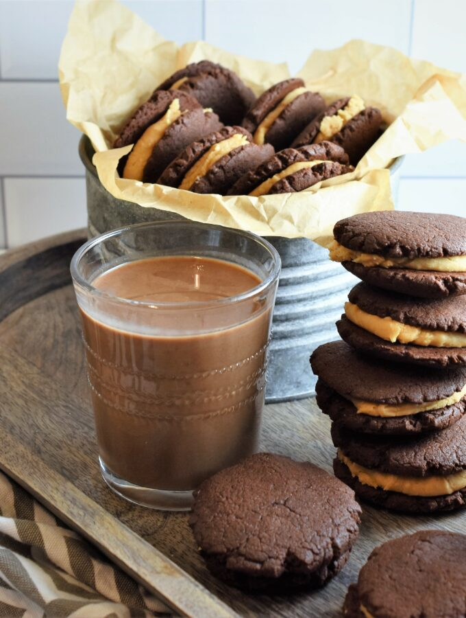 wood tray with vegan chocolate peanut butter sandwich cookies and chocolate almond milk