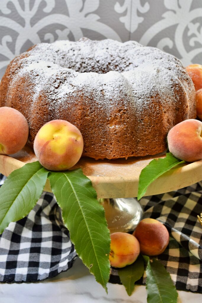 bundt cake sprinkled with powdered sugar on a cake stand garnished with fresh peaches