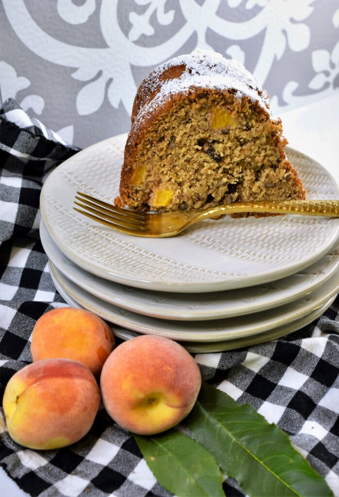 large slice of bundt cake on plate with peaches as garnish off to the side on a black and white gingham napkin