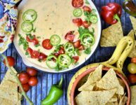 Hatch Chile Queso Blanco served in a red cast iron skillet with colorful napkin tied around handle with fresh cherry tomatoes and sliced jalopenos with tortilla chips