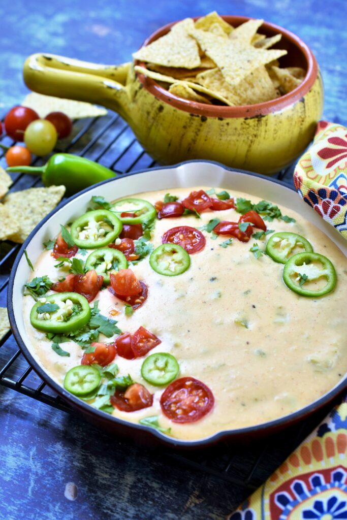 warm cheese dip served in a red cast iron skillet with colorful napkin tied around handle with fresh cherry tomatoes and sliced jalapenos with tortilla chips
