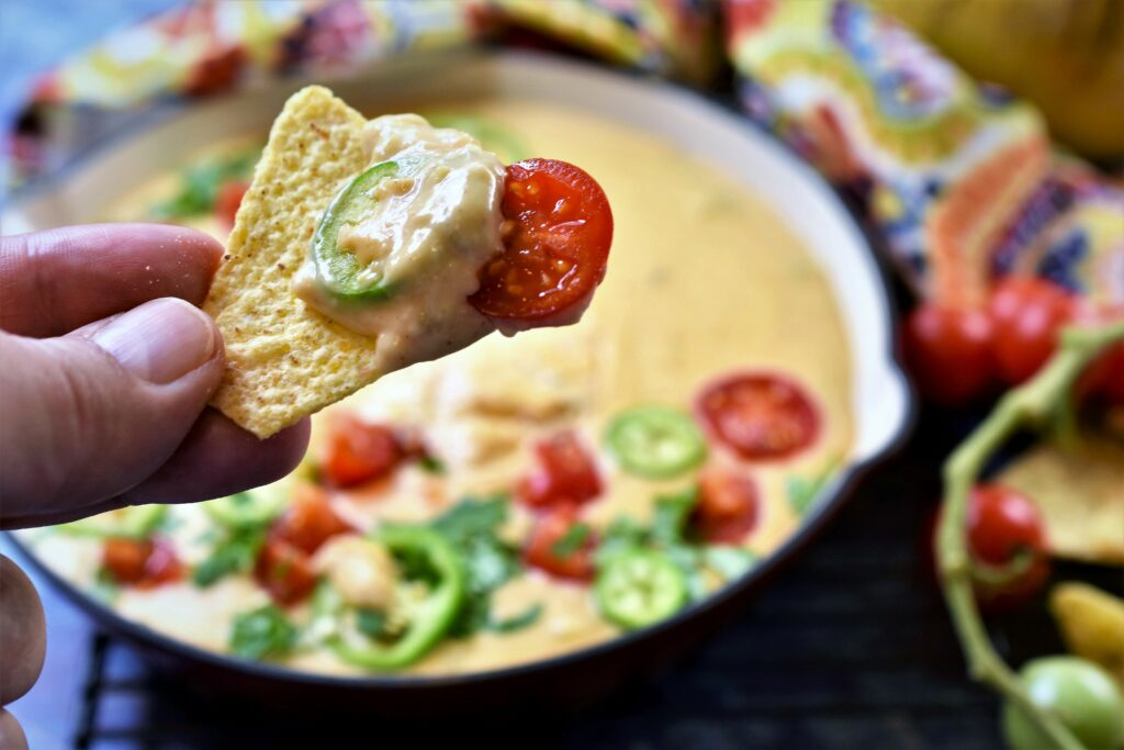 Hatch chile queso blanco scooped onto tortilla chip with jalapeno slice and cherry tomato slice