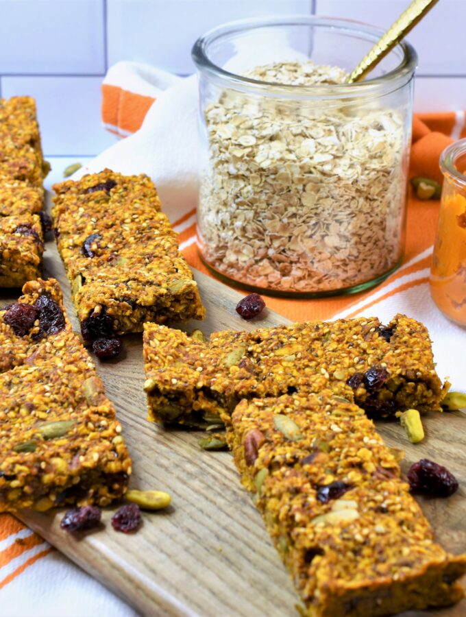 Fall oat bars with nuts and seeds on bread board with jar of oatmeal and jar of pumpkin puree