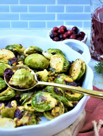 roasted Brussels sprouts with dried cranberries, pistachios and cranberry serrano vinegar in white ceramic side dish