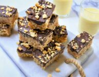 rice crispy treats with dark chocolate and peanut butter on white marble countertop