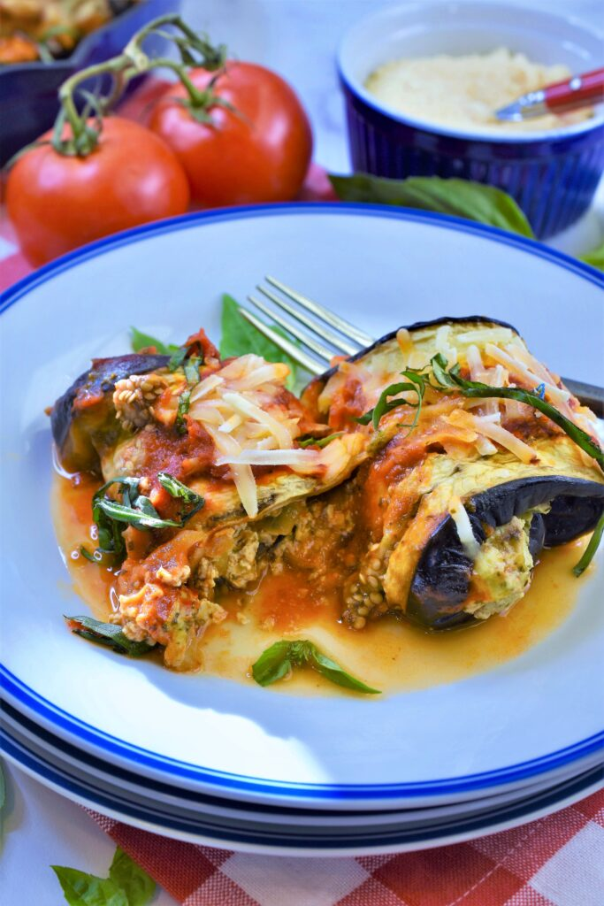 vegan cheese basil stuffed eggplant rollatini on white and blue plate